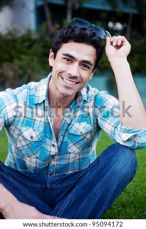 Happy young man sitting in grass