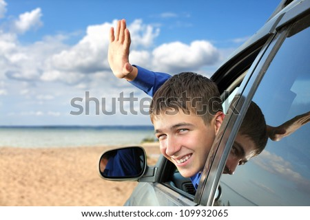 happy young man sitting in the car and wave goodbye - stock photo