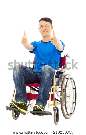happy young man sitting on a wheelchair and thumb up - stock photo