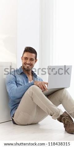 Happy young man sitting on floor at home, browsing internet, using laptop computer.