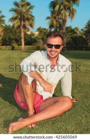 happy young man sitting on grass field in an exotic garden in the summer - stock photo