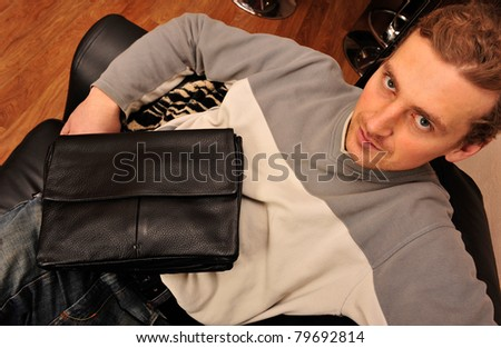Happy young man sitting on sofa at home and holding handbag - stock photo
