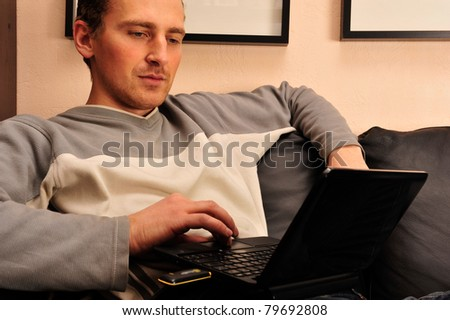 Happy young man sitting on sofa at home, working on laptop computer, smiling