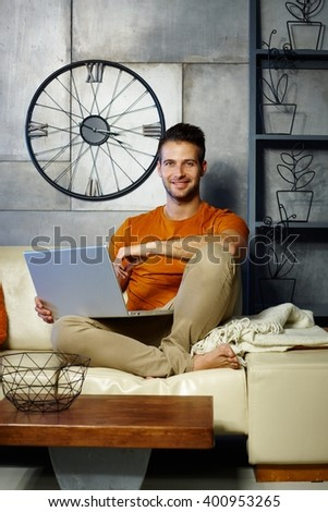 Happy young man sitting on sofa, holding laptop computer, smiling, looking at camera. - stock photo