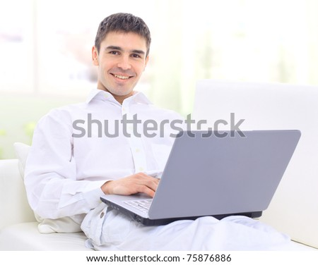Happy young man sitting on sofa with a laptop - stock photo