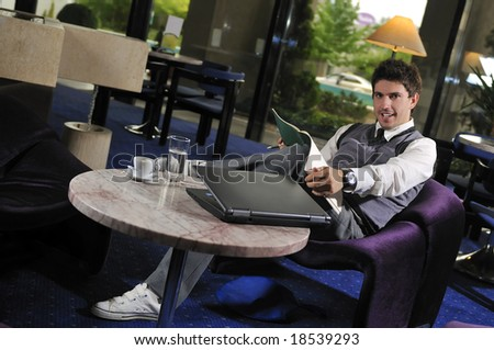 Happy young man sitting relaxed working on laptop computer - stock photo