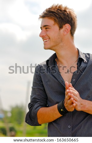 Happy young man smiling outdoors - stock photo