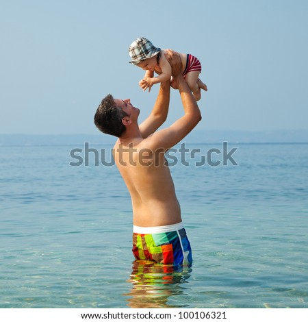 Happy young man standing in the sea and holding a smiling 9 months old baby - stock photo
