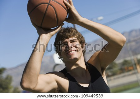 Happy young man taking a penalty shot with basketball - stock photo