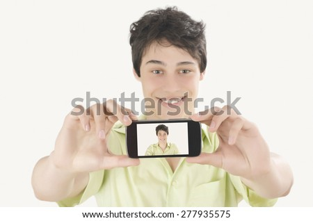 Happy young man taking a selfie photo with his smart phone. Man smiling looking at his mobile phone. Close up and focus on the mobile phone display. - stock photo