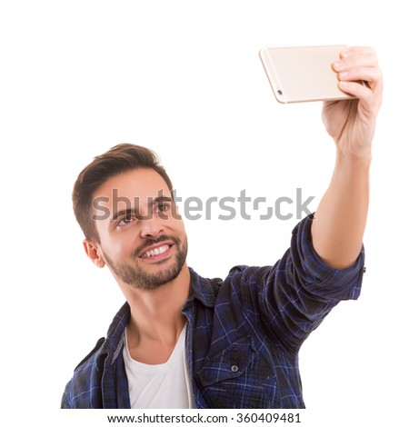 Happy young man taking self portrait photography through smart phone over white background.