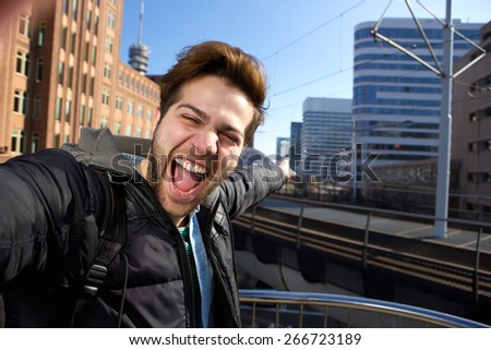 Happy young man taking selfie in the city during his travels - stock photo