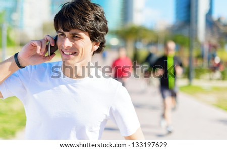 Happy Young Man Talking On Cellphone In Park - stock photo