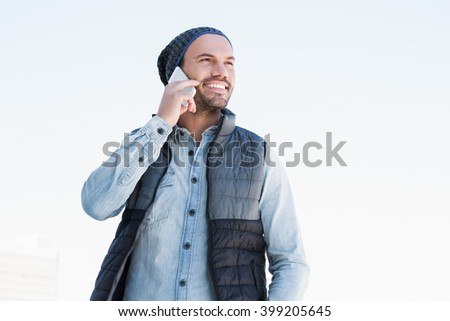 Happy young man talking on mobile phone on white background - stock photo