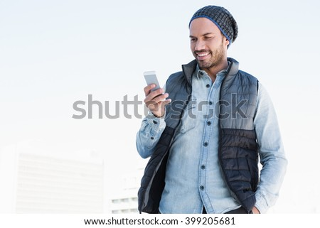 Happy young man text messaging on mobile phone - stock photo