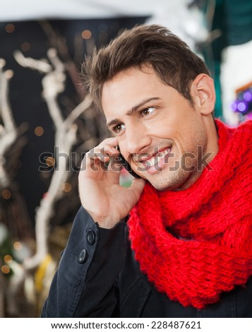 Happy young man using mobilephone in Christmas store - stock photo