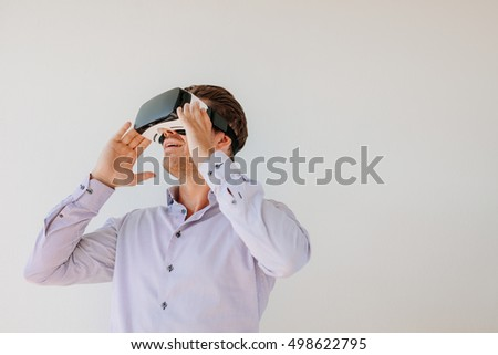 Happy young man using the virtual reality headset against grey background with copy space. Caucasian male model wearing VR goggles.