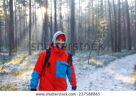 Happy young man walking in the forest  - stock photo