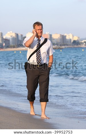 Happy young man walks and speaks close to the sea - stock photo