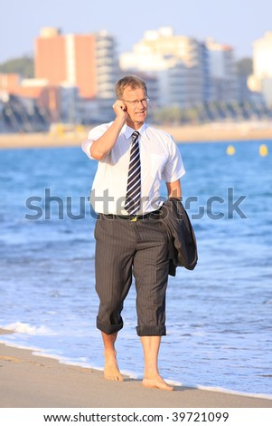 Happy young man walks close to the sea and make a phone call - stock photo
