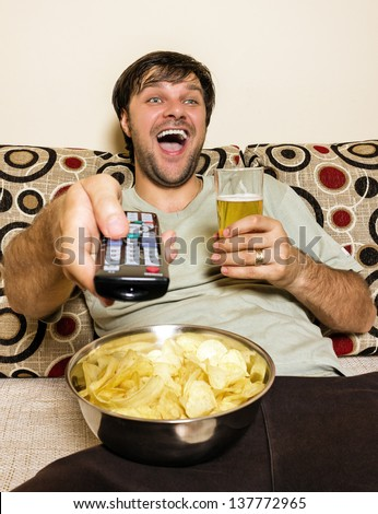 Happy young man watching television, eating potato chips and drinking beer inside - stock photo