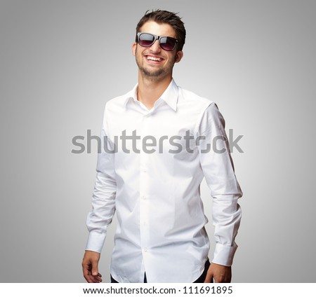 Happy Young Man Wearing Glasses On Gray Background - stock photo