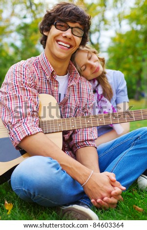 Happy young man with acoustic guitar and his romantic girlfriend in park outdoor - stock photo