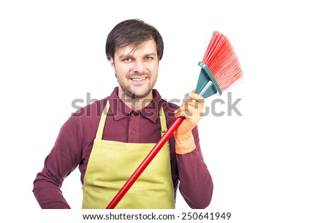 Happy young man with apron and gloves holding a sweep, ready to clean, over white - stock photo