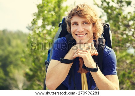 happy young man with backpack hiking in the mountains. sport outdoors - stock photo