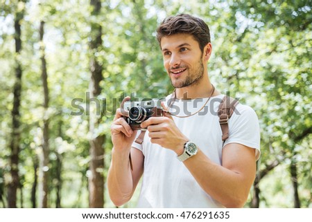 Happy young man with backpack taking pictures with old photo camera in forest