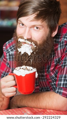 Happy young man with coffee and whipped cream on beard - stock photo