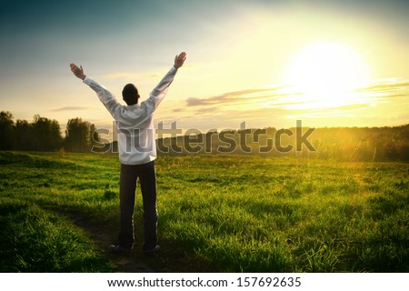 Happy Young man with hands up on sunset background
