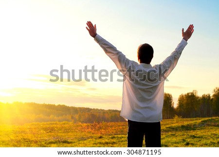 Happy Young Man with Hands Up on the Nature Background - stock photo