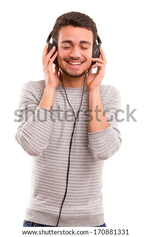 Happy young man with headphones on and listening to music