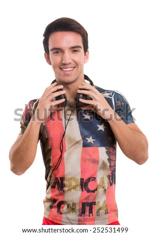 Happy young man with headphones on and listening to music - stock photo