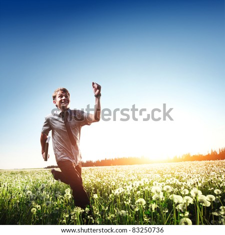 Happy young man with laptop in hand running on meadow with dandelions