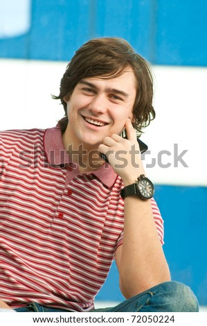 Happy young man with mobile phone, looking at camera - stock photo