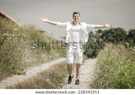 Happy young man with open arms and jumping  in a field  under  the summer  sun  - stock photo