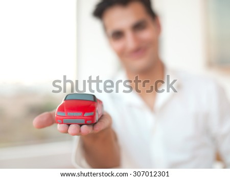 happy young man with red car - stock photo