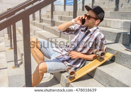 Happy young man with skate using smartphone