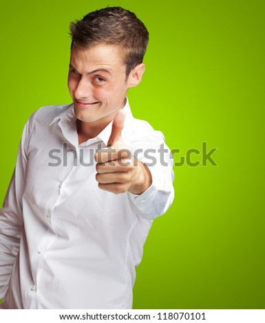 Happy Young Man With Thumbs Up On Green Background