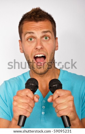 Happy young man with two microphoness singing karaoke