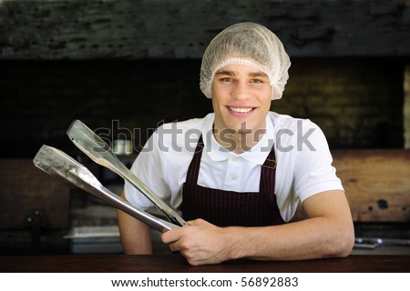 Happy young man working at a restaurant - stock photo