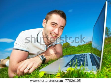 Happy young man working in the field. Beautiful summer sky. - stock photo