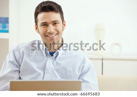 Happy young man working on laptop computer, smiling.? - stock photo
