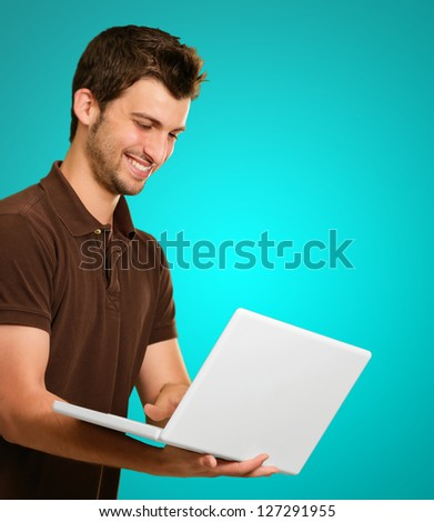 Happy Young Man Working On Laptop On Coloured Background
