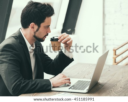 Happy young man working on laptop while sitting at his working place in office with coffee - stock photo