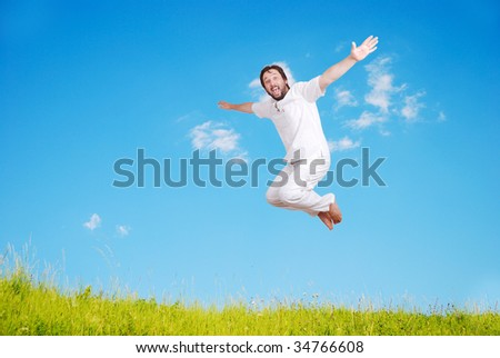 Happy young mane in white jumping on beautiful meadow - stock photo