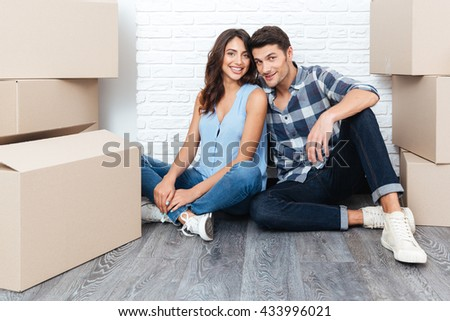 Happy young married couple moving in new house - stock photo