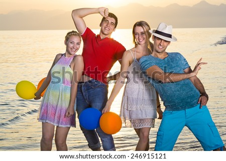 Happy Young Mates Posing at the Beach During Sunset Time. - stock photo
